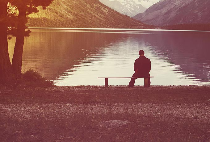 Young man sitting alone bereaved by suicide