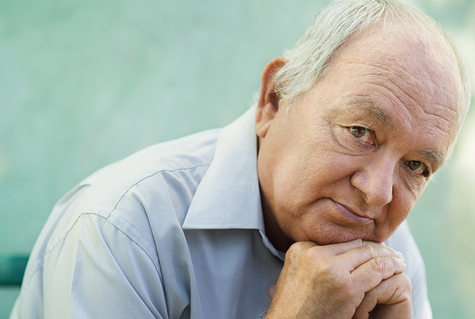 Older man with head on hands thinking about suicide warning signs