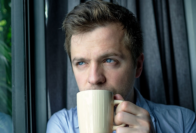 Man staring out window drinking coffee