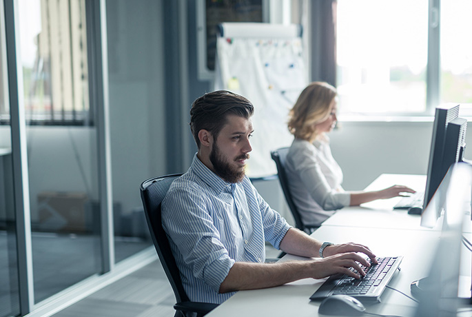 Man looking happy taking care sat at his desk at work