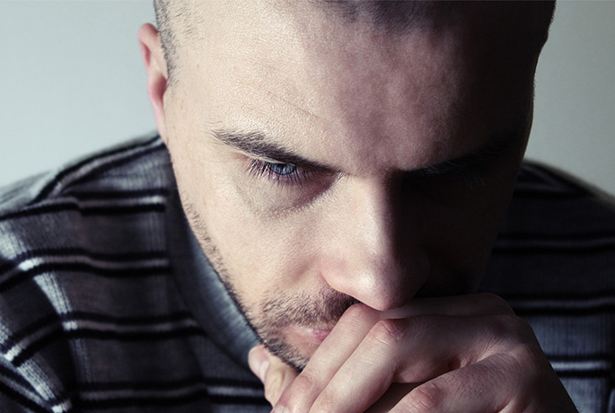 Man with head in hands feeling suicidal thinking about suicide