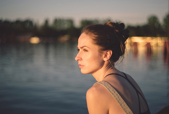 A woman sat looking out over a lake