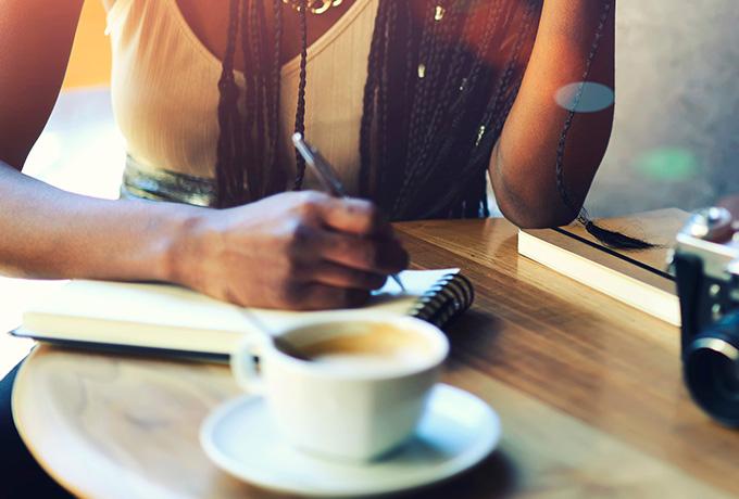 Women writing down her new years resolution