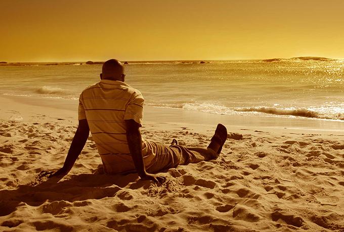 Man sat practicing mindfulness on a beach