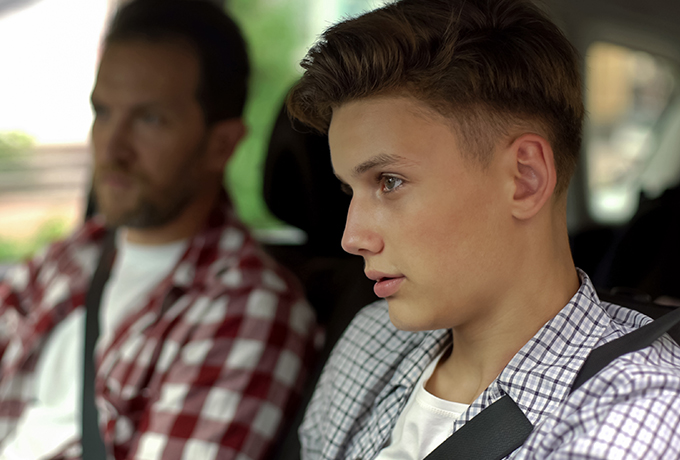 Father talking with son whilst driving