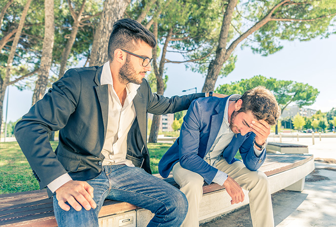 Two men sat together on a park bench